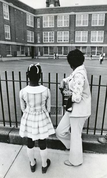 A woman and her daughter paused outside the fence before entering Gavin School in South Boston on Sept. 12, 1974, the first day of school under the new busing system put in place to desegregate Boston Public Schools.