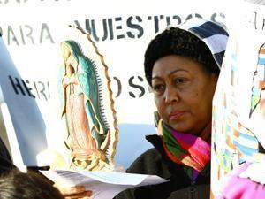 A woman holding a religious statue during the protest.