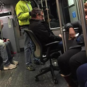 This image of a man lounging in an office chair on the Red Line was posted
