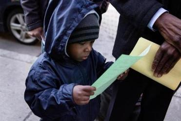 Telis Sebastian, 3, read a leaflet at the rally. He and his grandmother, Mary Pierre, live together and are facing displacement because of an unexpected increase in rent of $400.