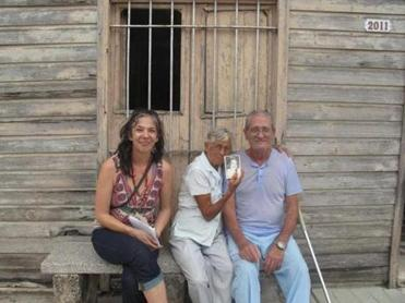 Lopez (left) during a 2011 visit to the town where her parents lived in Cuba. With her are Juanita Miranda — holding a photo of Lopez as a baby — and her husband, Alfonso, in front of their home.