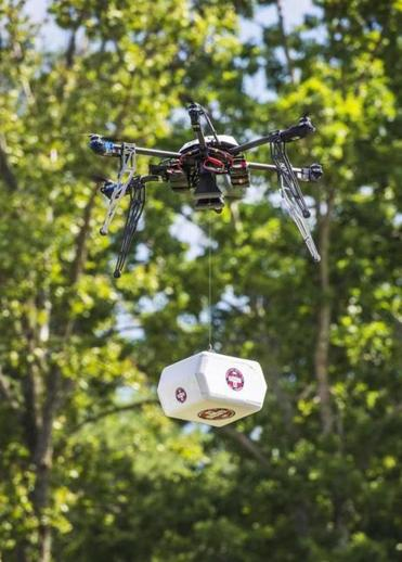 A Flirtey drone flies above the Wise County Fairgrounds while lowering a package of prescription medication at the Remote Area Medical Clinic in Wise County, Va. Flirtey is an independent drone delivery company.