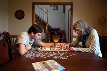 Cabral and his mother, Sandra Cabral, worked on a puzzle at their home.