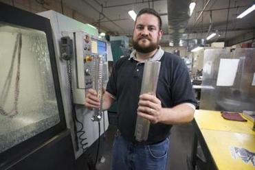 Yankee Hill Machine co-owner Chris Graham holds accessories for a semiautomatic weapon, before and after machining.