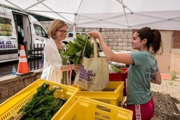 Alexandra Avedisian (left) of Brockton Neighborhood Health Center buys produce from Melissa Mardo, a Stonehill College student and an intern at its Mobile Market.
