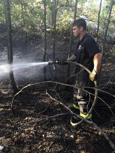 A firefighter worked Sunday to hose down the site of a brush fire that started Saturday.