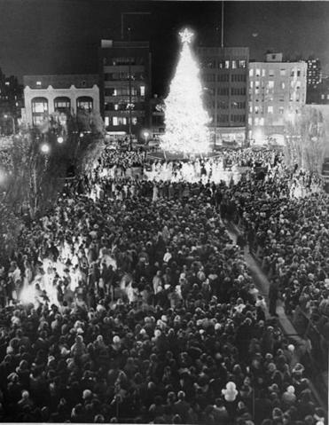 November 29 1977 / fromthearchive . Boston Globe Staff Photo by David Ryan / The opening of the Christmas season in Boston becomes official at the Prudential as Arthur Fiedler leads the crowd in carol singing at the sixth annual Christmas tree lighting ceremony. More than 15,000 lights decorate the 60 foot Canadian balsam fir tree, a gift to the city from the people of Nova Scotia. Dignitaries participating in the event include Mayor Kevin White, Cardinal Medeiros and Nova Scotia Premier Gerald A. Regan.