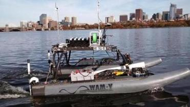 "MIT's autonomous boat Remote Explorer IV, nicknamed ""Rex,"" bristles with antennas and sensors as it navigates the Charles River basin. The 16-foot catamaran was used by the university and the Charles River Alliance of Boaters as part of a project to map the river bottom."