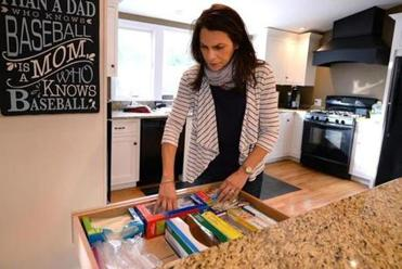 "Cohasset 12/19/2016 : Personal organizer, Lisa Dooley from ""Your Organized Life"" in Cohasset, looks through one of her organized kitchen drawers. Photo by Debee Tlumacki for the Boston Globe (south)"