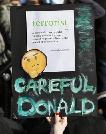 A woman holds up a sign with the definition of the word terrorist on it as she and others participate in an immigrants' rights' rally Sunday, Jan. 29, 2017, in New York's Battery Park. President Donald Trump's immigration order sowed more chaos and outrage across the country Sunday, with travelers detained at airports, panicked families searching for relatives while protesters registered opposition to the sweeping measure that was blocked by several federal courts. (AP Photo/Kathy Willens)