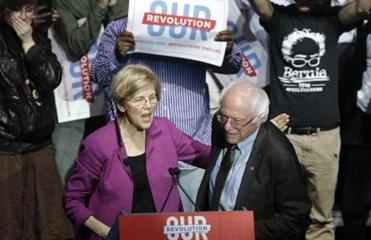 Sens. Elizabeth Warren, D-Mass., left, and Bernie Sanders, I-Vt., right, greet one another during a rally Friday, March 31, 2017, in Boston. Sanders and Warren made a joint appearance at the evening rally in Boston as liberals continue to mobilize against the agenda of Republican President Donald Trump. (AP Photo/Steven Senne)