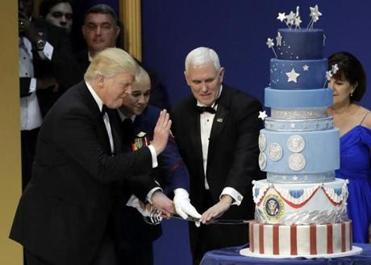 President Donald J. Trump, left, and Vice President Mike Pence, right, are helped by Coast Guard Petty Officer 2nd Class Matthew Babot, center, as they cut a cake at The Salute To Our Armed Services Inaugural Ball Friday, Jan. 20, 2017, in Washington. (AP Photo/David J. Phillip)