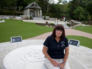 Gina Russo, who suffered severe burns and lost her fiancé in the Station nightclub fire, sat on a bench in the memorial in West Warwick, R.I.