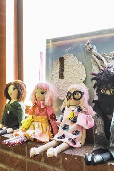 Handmade dolls — from Etsy shop Florette — depicting Erin Robertson and friends grace a windowsill in the living area.