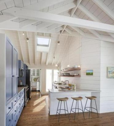 In the kitchen (facing page), Cube pendants from Tech Lighting add contemporary flair. The kitchen cabinetry is painted Benjamin Moore Stratford Blue. The counter stools are from West Elm.