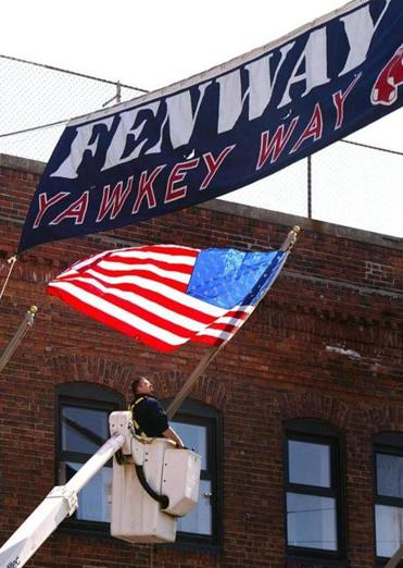 Boston-4/9/2005 Opening day at Fenway Park is monday, as work is ongoing to get the park in shape. David Candeias from Cambridge stands in a bucket truck as he hangs an American flag on a flag pole from Fenway Parks brick facade on Yawkey Way. Library Tag 08242005 Business