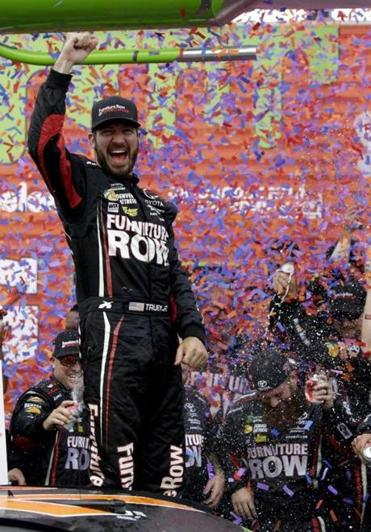 Martin Truex Jr., celebrates with his crew in Victory Lane after winning a NASCAR Cup Monster Energy Series auto race at Chicagoland Speedway in Joliet, Ill., Sunday, Sept. 17, 2017. (AP Photo/Nam Y. Huh)