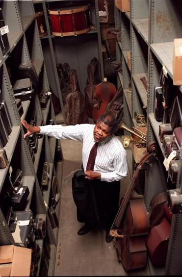 A warehouse containing hundreds of musical instruments for Boston Schools. Murphy Lewis head of musical instruments looks over shelves of instruments.