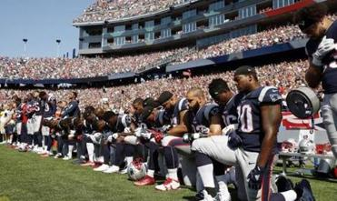 FILE - In this Sept. 24, 2017 file photo, several New England Patriots players kneel during the national anthem before an NFL football game against the Houston Texans in Foxborough, Mass. Patriots fans have burned team gear in protest after a number of players kneeled during the national anthem before last weekend's game. More than 100 people came out to Swansea, Massachusetts, on Thursday, Sept. 28 to throw Patriots T-shirts and other team apparel into a fire pit as they waved American flags and sang patriotic songs. (AP Photo/Michael Dwyer, File)