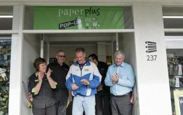 U.S. Ambassador to New Zealand and Samoa Scott Brown cuts a ribbon during an impromptu ribbon cutting at Philson and Kathryn Marsh's Paper Plus Pop up in Marton, New Zealand on Nov. 7, 2017. (Jeremy Lurgio)