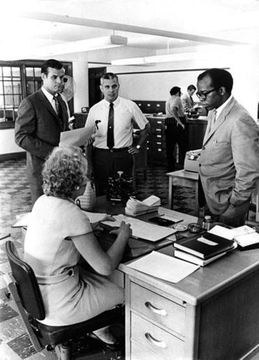 Boston City Councilors Joseph Timilty, standing left, and Tom Atkins, standing right, tour the Boston Police Department with Captain Charles Cobb, center, on Aug. 7, 1969.