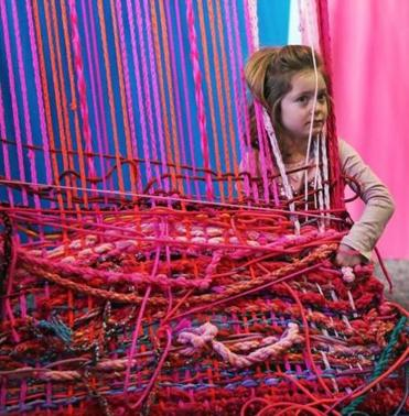 Zoe Thompson of Somerville took part in a weaving demonstration at the Children's Museum.