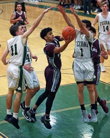 Attleboro,MA 1-8-18: Damien Perry (center) of Bishop Stang is pictured as he drives between the defense of Bishop Feehan's Luke Sullivan (11), Matthew Carroll (44) ad Paul Roche (1) in the first quarter. Bishop Stang visited Bishop Feehan in a boy's high school basketball game. (Jim Davis/Globe Staff)