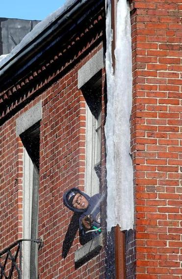 A person worked to douse hot water over ice on a Beaon Hill building.