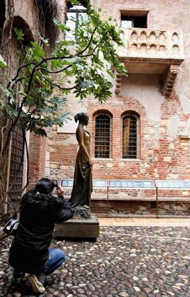 A tourist takes a picture of the bronze statue of Juliette Capulet under the balcony of her house.