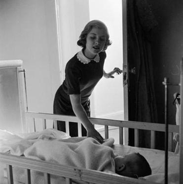 Circa 1948: A baby-sitter keeps a watchful eye on a sleeping child.