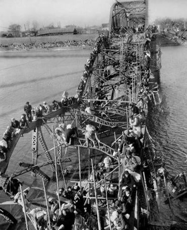 In 1950, Mr. Desfor climbed a 50-foot-high section in order to photograph refugees fleeing for their lives across a bridge along the Taedong River that had been damaged by bombing.