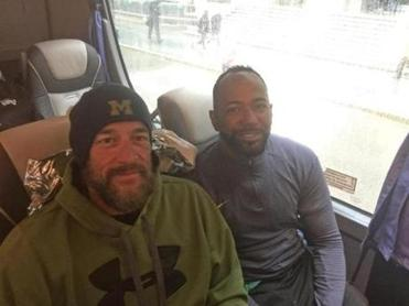 "Army veterans Tom Davis and Alfredo ""Freddie"" De Los Santos, warming up on a bus after a wet, cold race, finished first and second in the handcycle division of the Boston Marathon for the second consecutive year."