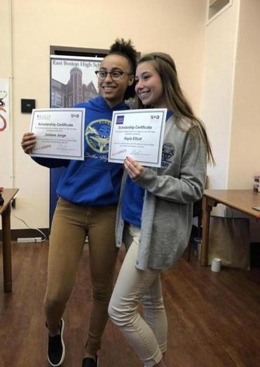 East Boston High School Seniors Juliane Jorge and Kayla Elliott were surprised by the Scholar Athletes organization with full tuition scholarships to Regis College and Curry College, respectively.