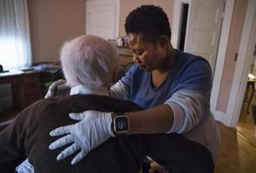 Newton, MA - 2/4/2018 Rita Sarpong tends to her 90-year-old patient at his home in Newton, MA, Feb. 4, 2018. Sarpong, a Ghanaian immigrant, works two jobs as a home health care aide. (Keith Bedford/Globe Staff) homeaides