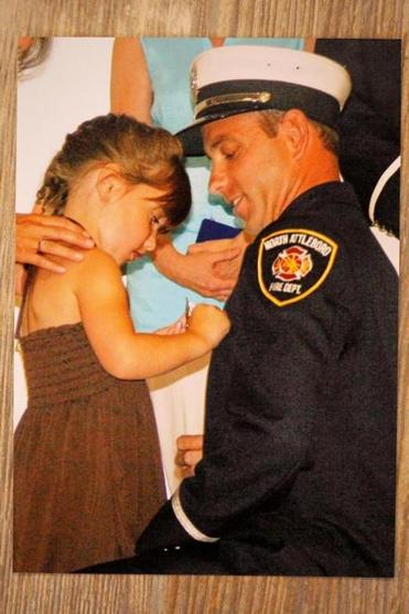 A personal photo shows Captain Rick Stack getting pinned with his young daughter when he was promoted.
