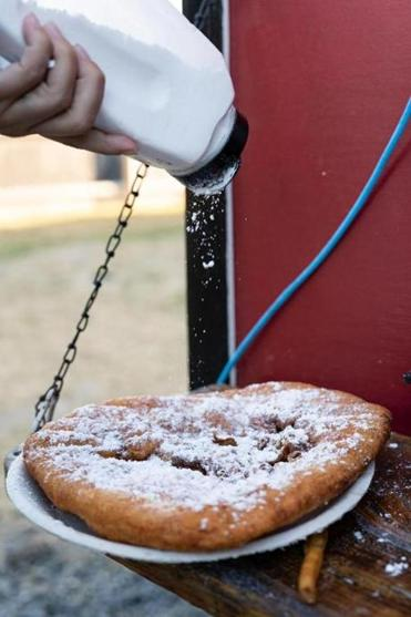 A patron puts powdered sugar on fried dough from Big Grampa's Grill food truck at Congdon's After Dark in Wells.