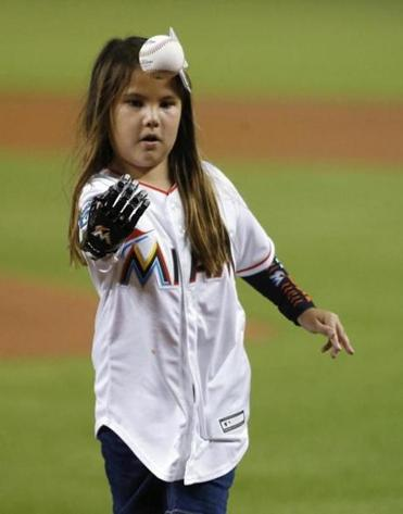 Hailey Dawson, 8, uses her 3-D printed robotic hand to throw out the first pitch before a baseball game in Miami on Aug. 10.