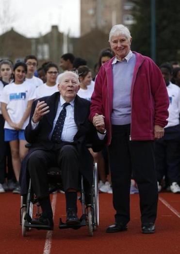 Former British athletes Sir Roger Bannister, center left, and Diane Charles, center right, pose with school children during the launch of the Westminster Mile run, to celebrate the 60th anniversary of Bannister's record of being the first man to run a sub-four minute mile and Diane Leather's (now Diane Charles) record of being the first woman to run a sub-five minute mile in May 1954, at Paddington Recreation Ground in London, Wednesday, Feb. 26, 2014. The Westminster Mile run is to be held in May 2014 through the streets of London. (AP Photo/Sang Tan)