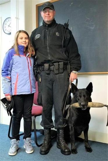 Olivia Feil, 9, with Trooper Thomas Janeczak and Tank, his K-9 partner.