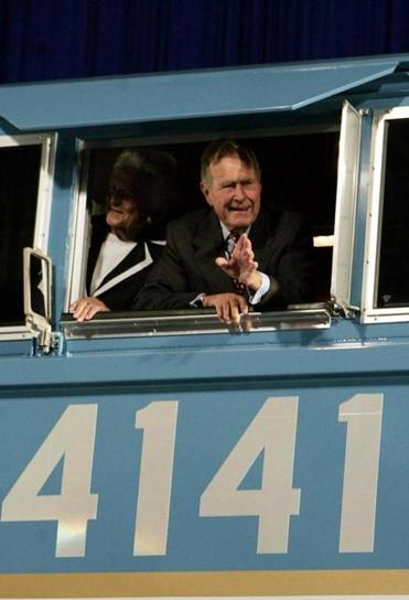 FILE - In this Oct. 18, 2005, file photo, former President George H.W. Bush and his wife Barbara wave out the window of a new locomotive numbered 4141 in honor of the 41st president at Texas A&M University in College Station, Texas. The 4,300-horsepower machine will carry Bush's remains Thursday, Dec. 6, 2018, to his final resting place. The locomotive is traveling from suburban Houston about 70 miles (113 kilometers) to College Station, where Bush will be buried at his presidential library. (AP Photo/Pat Sullivan, File)