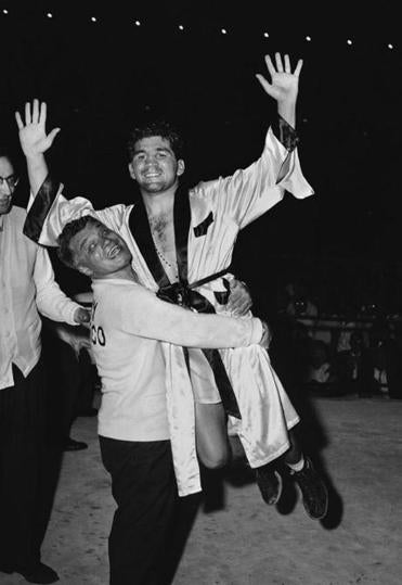 FILE - In this June 16, 1956, file photo, Tony Demarco is lifted by trainer Sammy Fuller following his unanimous 10-round decision over Vince Martinez at Fenway Park in Boston. DeMarco was selected for induction into the Boxing Hall of Fame, in the old-timer category, Wednesday, Dec. 5, 2018. (AP Photo/File)