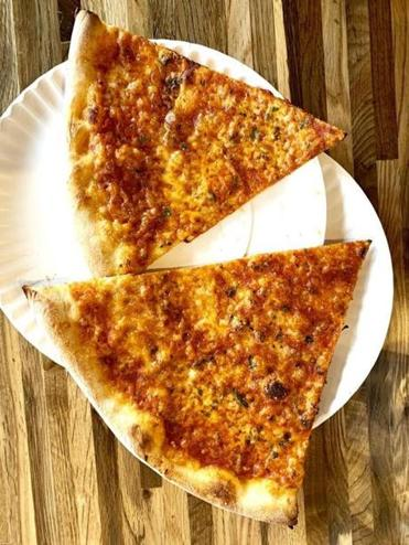 Two slices of the Standard, made with red sauce, Parmesan, aged mozzarella, and fresh herbs.