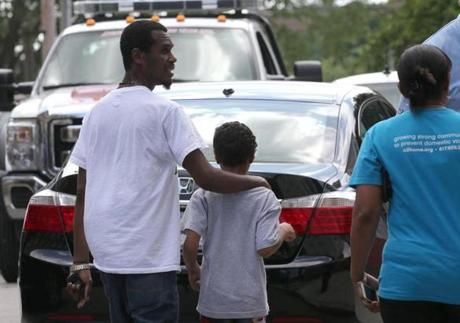 BOSTON, MA - 8/12/2016: Kelvin Martins with his uncle Luando Da Costa is led away to vehicle after being released by EMT's . The 9-year-old boy was located and is safe and sound after his father allegedly took him from a sooting scene in his car, police said. Juan Ayala-Powell, 27, left a shooting Thursday night on Blue Hill Avenue with his son, Kelvin Martins, in the green 2004 Ford Explorer. (David L Ryan/Globe Staff Photo) SECTION: METRO TOPIC 13shooting(2)