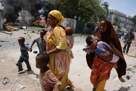 GRAPHIC CONTENT Two mothers run with their children on April 14, 2013, in Mogadishu, after a suicide bomber attack in the regional court premises that left several dead. Gunmen wearing suicide vests stormed the main court complex in Mogadishu on April 14, killing at least five people before holing themselves up as Somali and African forces surrounded the building. Several people were wounded minutes later when a remote-detonated car bomb went off as a Turkish aid convoy drove by near the airport, in some of the worst violence to hit Mogadishu in months. AFP PHOTO / MOHAMED ABDIWAHAB (Photo credit should read Mohamed Abdiwahab/AFP/Getty Images)