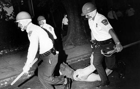 Boston, MA - 6/2/1967: Boston Police officers wearing riot helmets and carrying batons arrest rioters in Roxbury on June 2, 1967. (Bob Dean/Globe Staff) --- BGPA Reference: 140902_MJ_022