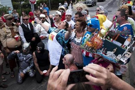 Gloucester, MA - 6/25/17 - Gloucester Mayor Sefatia Romeo Theken (cq) leads a chant with her constituents during the St. Peter's Fiesta in Gloucester, Mass. on Sunday, June 25, 2017. Each year a select group of men, some novices, others seasoned champions, compete against each other to see who can run across a telephone pole layered in grease and suspended over the sea. This year after one full round, Gloucester resident, Jake Wagner, grabbed the flag, claiming victory. (Nicholas Pfosi for The Boston Globe) Reporter: Billy Baker Topic: 02greasypole(2)