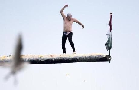 Gloucester, MA - 6/25/17 - Randy Sweet, the winner of Friday's and Saturday's competition during the practice round on Sunday on the greasy pole during the St. Peter's Fiesta in Gloucester, Mass. on Sunday, June 25, 2017. Each year a select group of men, some novices, others seasoned champions, compete against each other to see who can run across a telephone pole layered in grease and suspended over the sea. This year after one full round, Gloucester resident, Jake Wagner, grabbed the flag, claiming victory. (Nicholas Pfosi for The Boston Globe) Reporter: Billy Baker Topic: 02greasypole(2)