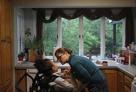 Dracut, Ma., 06/06/17, After carrying Abi down the stairs to the kitchen, Noelia brushes Abi's teeth, fixes her hair and delivers medications into her feeding tube. Suzanne Kreiter/Globe Staff