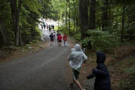 Orford, NH - 7/17/17 - Campers head down to dinner during a rainy afternoon at Camp Moosilauke on Monday, July 17, 2017. Because of the weather, the power was temporarily knocked out but campers continued on with flash lights, hardly missing a beat. (Nicholas Pfosi for The Boston Globe) Reporter: Tom Farragher Topic: 19Farragher