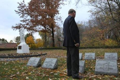 (FOR FUTURE PROJECT. DO NOT PUBLISH.) Teweksbury, MA., 11/16/2016, Jim Graham visits the grave of his father. He discovered that his biological father was a priest, Father Thomas S. Sulllivan. (Suzanne Kreiter/Globe staff)